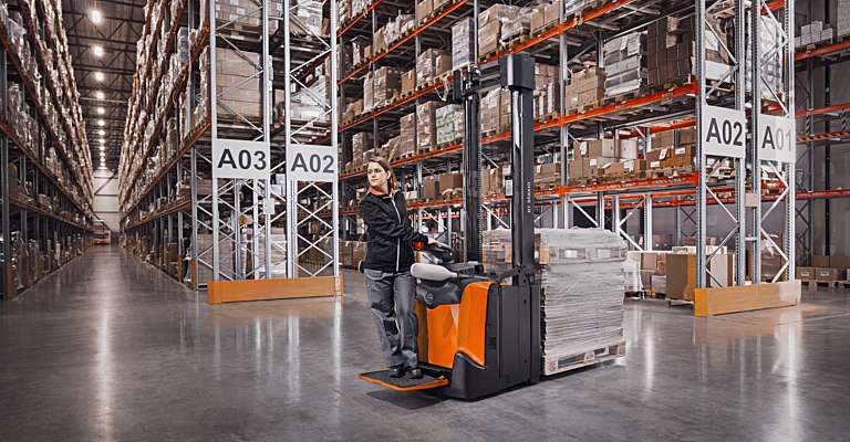 Woman driving a Staxio stacker in warehouse