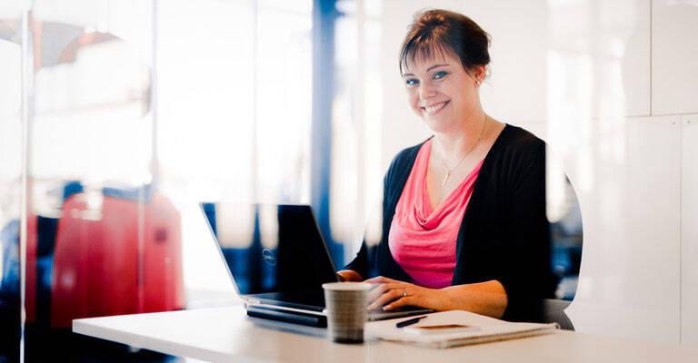 Kvinde sidder ved skrivebord og smiler