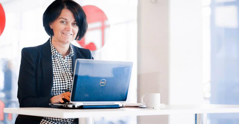 Frau sitzt mit Laptop am Tisch
