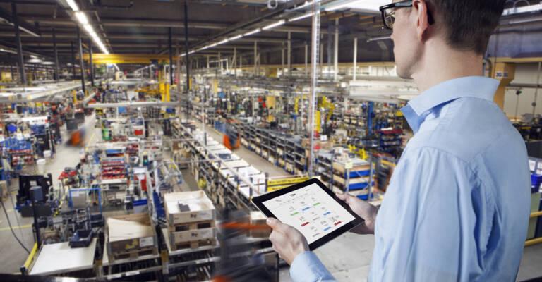 Hombre mirando un almacén viendo I-Site en la tablet