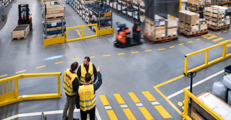 Employés logistiques qui apprennent le Lean Management en entrepôt avec les conseillers de Toyota