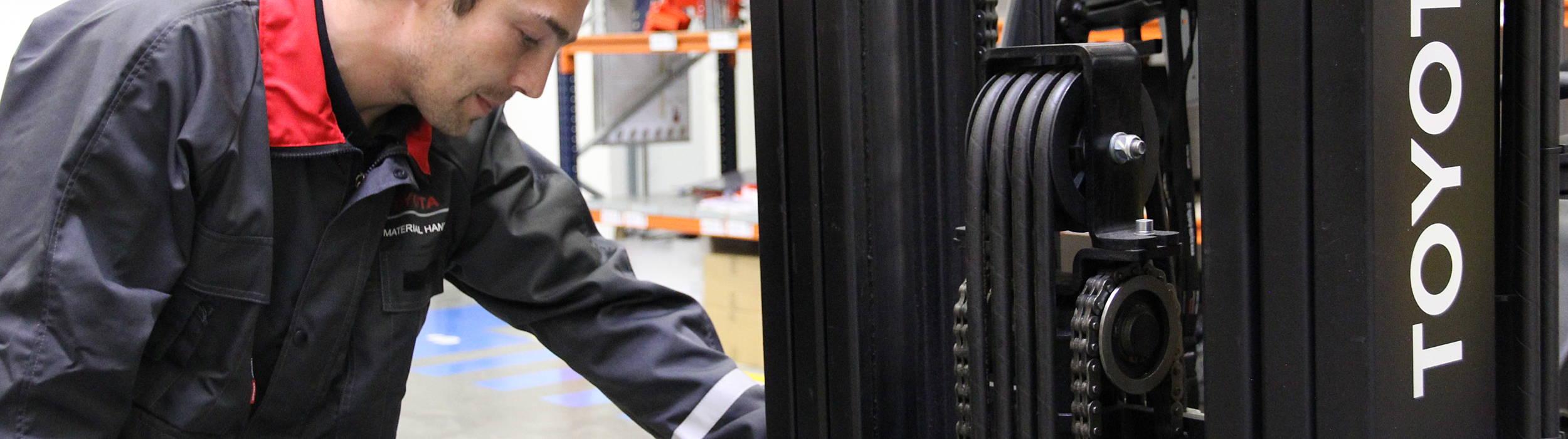 Servisní technik ve skladě kontroluje stav vysokozdvižné vozíku - bezpečnost