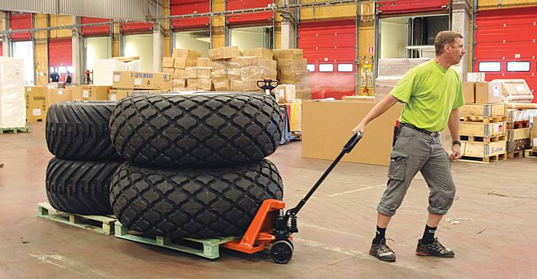 workman carrying tyres through a warehouse