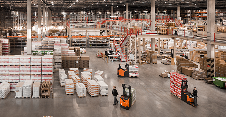 Almacén con máquinas transportando mercancías