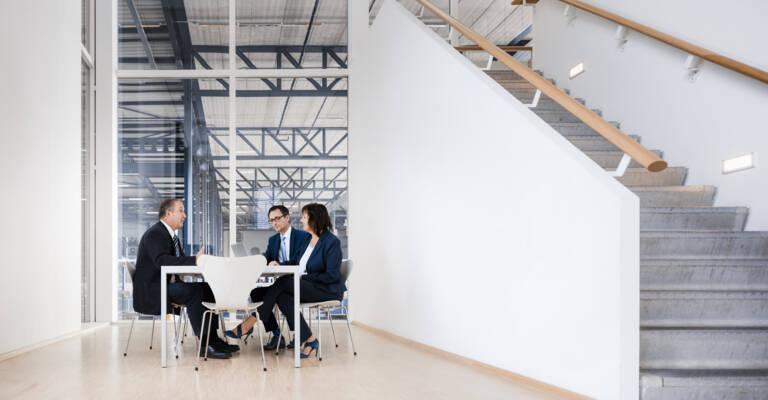 A dolgozók egy asztal mellett ülnek